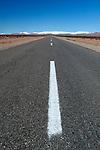 Morocco, Souss-Massa-Draa, near Tineghir: Straight road running through desert with snow-capped Atlas mountains in distance | Marokko, Souss-Massa-Draa, bei Tineghir: Landstrasse verlaeuft schnurgerade durch die Wueste, die schneebedeckten Gipfel des Hohen Atlas Gebirges im Hintergrund