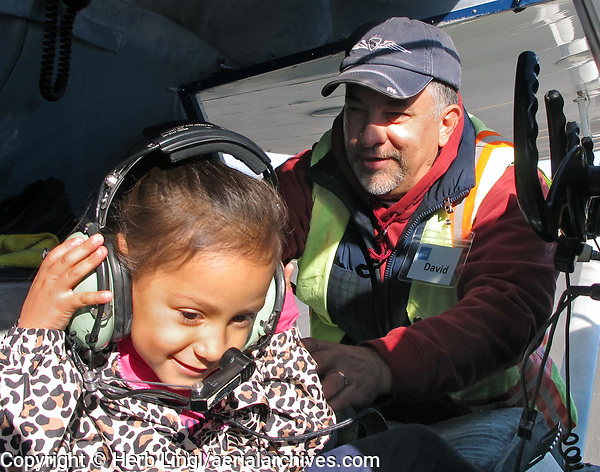 Pilot David Flaig helps a girl too young for a Young Eagles flight (less than 8 years old) experience what it's like to be in the cockpit of an airplane during the Experimental Aircraft Association Young Eagles rally at Lampson Field (102), Lakeport, Lake County, California
