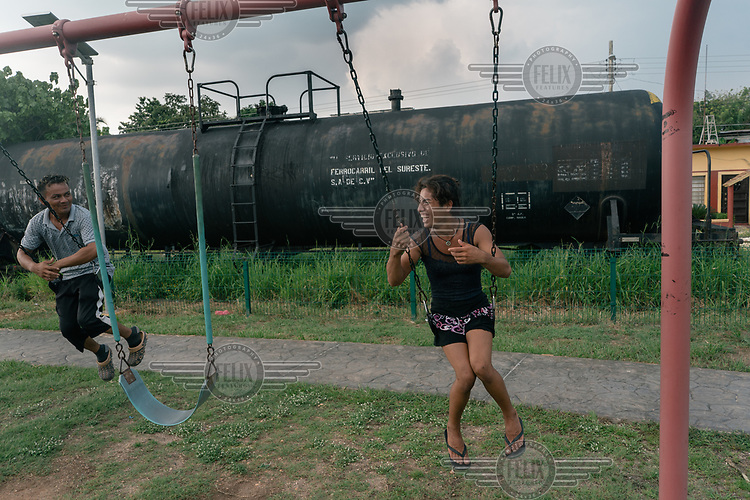 Dulce (16), an unaccompanied Guatemalan migrant, and her friend Jones (32), a Honduran migrant, play on children's swings near some train tracks. Dulce is a transgender woman who left Guatemala for a second time after she suffered from domestic violence in her family and received death threats in her small town.