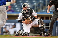 Tulsa Drillers catcher Dustin Garneau (13) looks to a runner attempting to score after receiving a throw during a game against the Midland RockHounds on May 30, 2014 at ONEOK Field in Tulsa, Oklahoma.  Tulsa defeated Midland 7-1.  (Mike Janes/Four Seam Images)