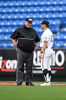 Michigan Wolverines head coach Erik Bakich (23) questions a call with umpire Dorsey Hager during the first game of a doubleheader against the Siena Saints on February 27, 2015 at Tradition Field in St. Lucie, Florida.  Michigan defeated Siena 6-2.  (Mike Janes/Four Seam Images)