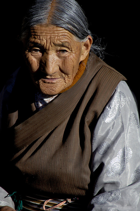 Waiting for the day to go by, an old women sitting at a trditional house entrance  Lhasa, Tibet