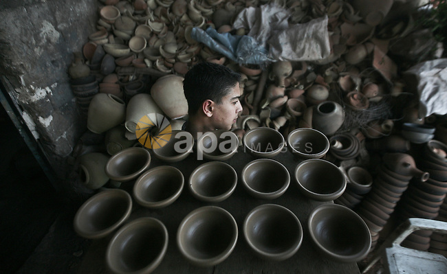 Palestinian Sabri Atallah, stores pots built with natural clay at his grandfather's shop 'Atallah Pottery', in Gaza Strip on 24 February 2012. Atallah pottery shop is one of the biggest pottery shops in Gaza strip. Children and grand children of Atallah work at the pottery shop and make pots, vases and many other clay works. Photo by Ali Jadallah