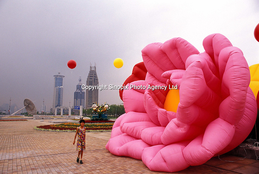 A girl walks past a half-inflated giant plastic flower. It is part of a municipal effort to brighten up the Pudong district of Shanghai, China..20-MAY-02