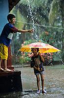 Asien Indien IND Karnataka, Kinder spielen mit Regenschirm im Monsun Regen / India Karnataka - children with umbrella play in Monsoon rain