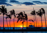 A warm and windy spot under palm trees near a sailboat at the beach is the perfect place to watch a colorful summer sunset, Big Island of Hawai'i.