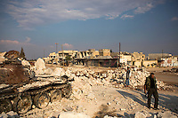 Free Syrian Army (FSA) fighters and civilians climb on destroyed regime tanks in the rubble of a destroyed mosque in the recently liberated town of Azaz near the Turkish border.