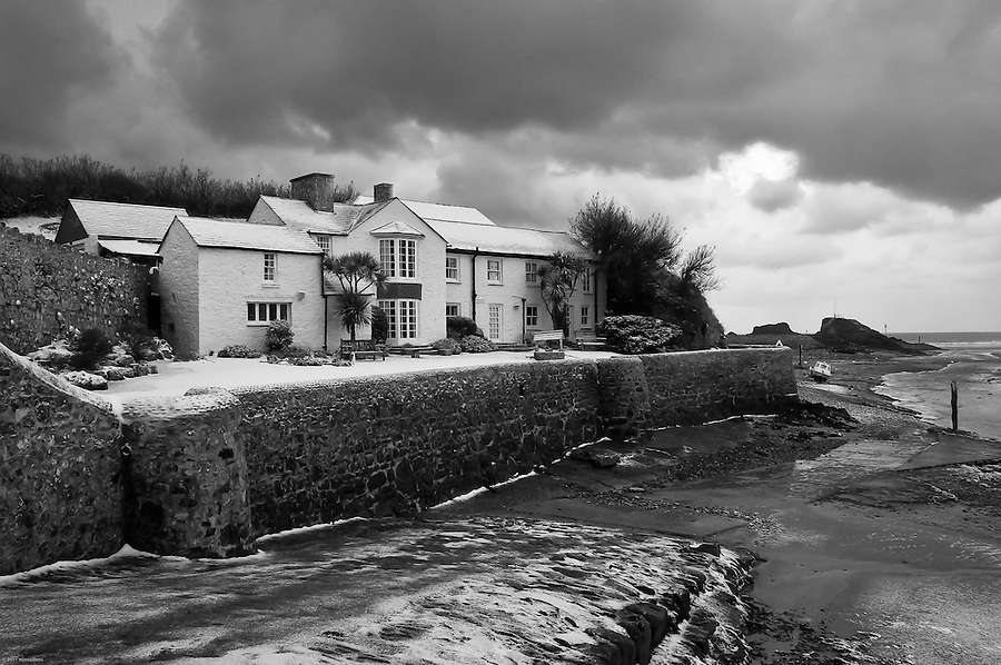 Storm clouds gathering and about to drop further snow on historic Efford Cottage, which lies at the end of the Bude Canal and on the side of Summerleaze Beach. The River Neet flows out past Chapel Rock at the end of the breakwater in the background.