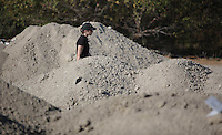 Pictured: A forensics officer walks through the piles of soil that need to be searched through by in Kos, Greece. Thursday 06 October 2016<br />