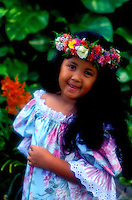 A beautiful smiling young Hawaiian girl dressed in a muu muu and wearing a haku lei (floral headpiece) stands in front of green foliage.