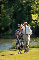 Older couple enjoy a walk through a park.