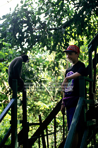 Ariau Tower Jungle Lodge Hotel, Rio Negro, Amazonas State, Brazil. Boy and woolly monkey looking at each other.