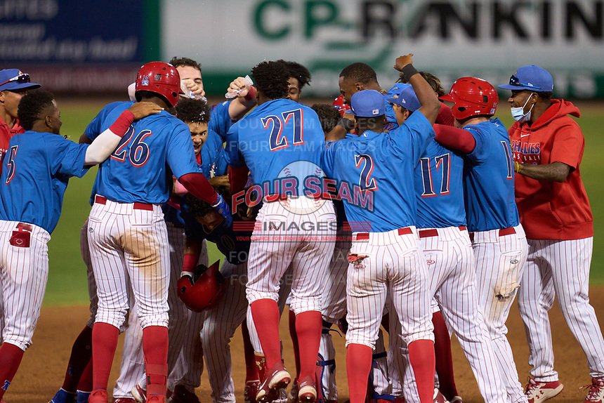 Clearwater Threshers Abrahan Gutierrez (10) is mobbed by teammates after hitting a walk-off single during a game against the Dunedin Blue Jays on May 18, 2021 at BayCare Ballpark in Clearwater, Florida.  (Mike Janes/Four Seam Images)