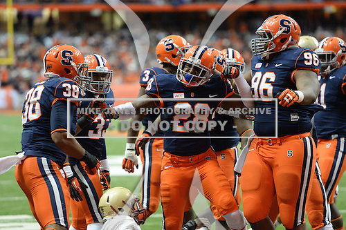 Syracuse Orange strong safety Jeremi Wilkes (28) celebrates after making a tackle with teammates Cameron Lynch (38) and Jay Bromley (96) during a game against the Boston College Eagles at the Carrier Dome on November 30, 2013 in Syracuse, New York.  Syracuse defeated Boston College 34-31.  (Copyright Mike Janes Photography)