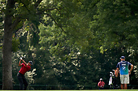 OLYMPIA FIELDS, IL - AUGUST 30: Tiger Woods of the United States plays his second shot from the fairway of the 15th hole as caddie Joe LaCava looks on during the final round of the BMW Championship on the (North) Course at Olympia Fields Country Club