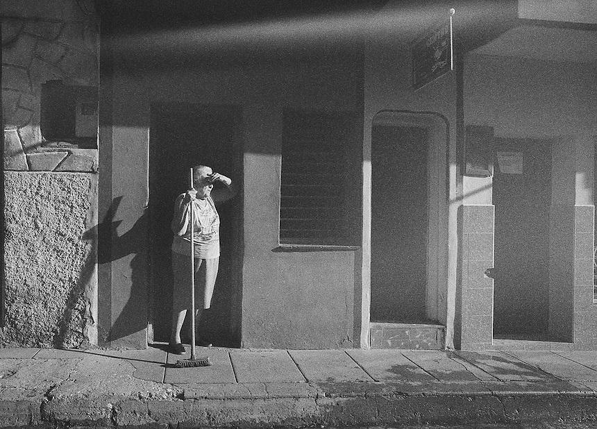 A woman takes a break while sweeping her walk in Santa Clara, Cuba. MARK TAYLOR GALLERY
