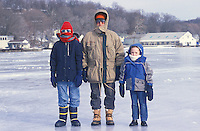 Three people standing on a frozen lake.