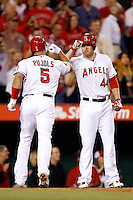 Albert Pujols #5 of the Los Angeles Angels is greeted by teammate Mark Trumbo #44 after scoring during a game against the Kansas City Royals at Angel Stadium on May 14, 2013 in Anaheim, California. (Larry Goren/Four Seam Images)