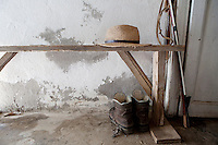 Hat and boots wait on a bench by the door in the shepherd's cabin where Bernard Bruno, sheep raiser, lives during 3 summer months while his sheep graze the mountain pastures around the Plateau de Longon, Mercantour National Park, French Alps, France, 01 August 2013