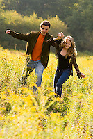 Couple running through field of goldenrod<br />
