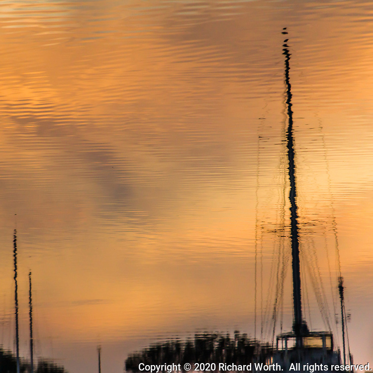 Rippling water reflects and distorts a sailboat mast at sunset.  San Leandro Marina on San Francisco Bay. Square perspective.