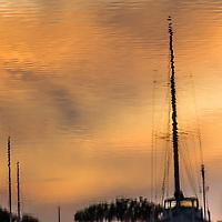 Rippling water reflects and distorts a sailboat mast at sunset.  San Leandro Marina on San Francisco Bay. Square perspective.