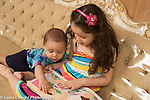 5 year old girl showing picture book to her 7 month old brother