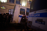 Police stand near transportation buses as they watch protesters during an illegal protest against Putin in Lubyanka Square in Moscow, Russia.