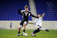 Max Wasserman (22) of the Connecticut Huskies goes for a tackle on Colin Rolfe (9) of the Louisville Cardinals. Connecticut defeated Louisville 1-0 during the first semifinal match of the Big East Men's Soccer Championships at Red Bull Arena in Harrison, NJ, on November 11, 2011.