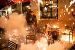"Fireworks thrown by anti-Trump demonstrators in the direction of Trump supporters explode in the outdoor dining are of a P.J. Clarke's, interrupting dinner, during the ""Million MAGA March"" on November 14, 2020 in Washington, D.C.  Thousands of supporters of U.S. President Donald Trump gathered to protest the results of the 2020 presidential election won by President-Elect Joe Biden.  Photograph by Michael Nagle"