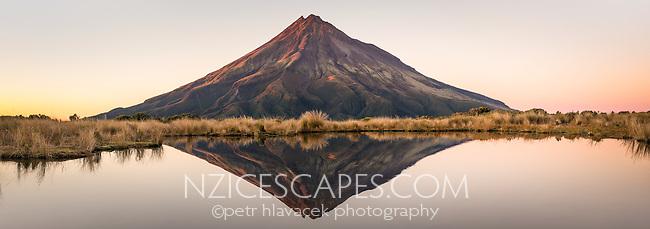 Sunrise over Taranaki, Mt. Egmont with reflections in alpine tarn, Egmont National Park, North Island, New Zealand, NZ