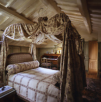 A Louis XVI bed dominates the attic master bedroom, its metal hoops draped with 18th-century toile de Jouy