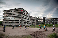 A football (soccer) game being played in the grounds of the former Grand Hotel building. Once a luxury destination for the wealthy and the continent's biggest hotel, the building is now a concrete shell and home to about 6,000 squatters. Those unable to occupy one of the rooms sleep in the corridors, basements and even on the roof of the building.