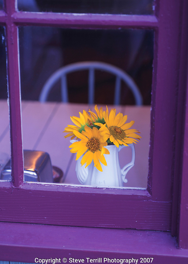Vase of sunflowers on table looking through window