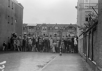 Photo from the NIOD's Huizinga collection. Audience looks over the wall at the Canadian Liberation Parade in the rain.