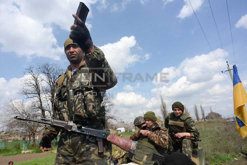 Ukrainian forces are being blocked by local citizens near Kramatorsk city during the anti-terrorist operation. A soldier demonstrates peaceful intentions towards civilians showing unloaded ammunitions magazines