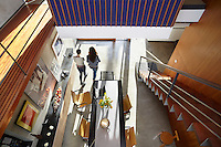 Two women are seen from above walking through an open plan dining which incorporates a cantilever staircase on one side.