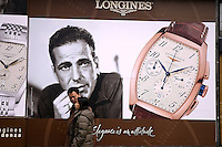 Couple passing image of Humphrey Bogart in advertising for Swiss luxury watch brand Longines.