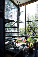 A quiet landing filled with geraniums and surrounded by floor-to-ceiling windows is furnished with a Le Corbusier chaise longue
