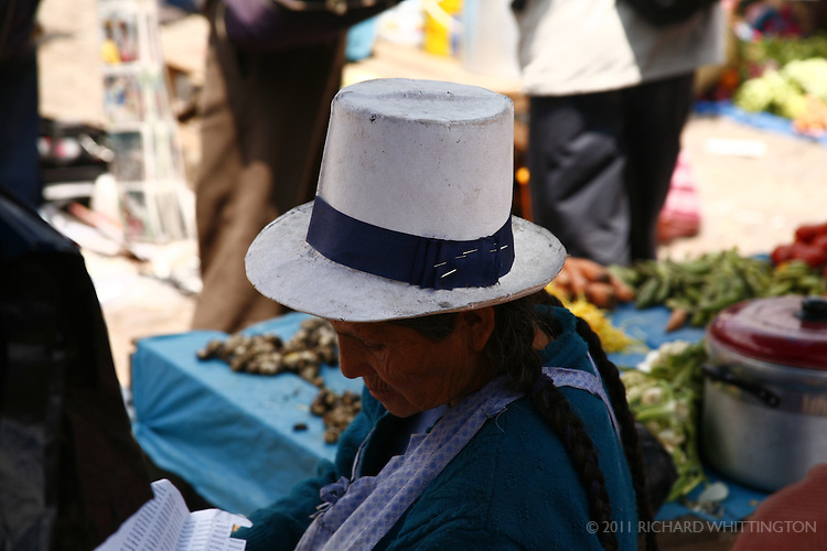 A women at the Pisac market weaing an unusual hat.