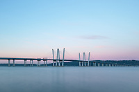 A view of the  Governor Mario M. Cuomo Bridge spanning the Hudson River at sunrise with sunlit clouds overhead.