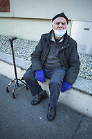 """Switzerland. Canton Ticino. Lugano. An elderly man wears a mask on the face and gloves on his hands to protect himself from the Coronavirus (also called Covid-19). He seats on a his concrete wall and takes a rest. Due to the spread of the coronavirus, the Federal Council has categorised the situation in the country as """"extraordinary"""". It has issued a recommendation to all citizens to stay at home, especially the sick and the elderly. The Federal Council (German: Bundesrat, French: Conseil fédéral, Italian: Consiglio federale, Romansh: Cussegl federal) is the seven-member executive council that constitutes the federal government of the Swiss Confederation. 17.03.2020 © 2020 Didier Ruef"""