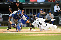 Toronto Blue Jays catcher Dioner Navarro (30) loses the ball attempting to tag Dayan Viciedo (24) sliding home safely as umpire Tim Welke looks on during a game against the Chicago White Sox on August 15, 2014 at U.S. Cellular Field in Chicago, Illinois.  Chicago defeated Toronto 11-5.  (Mike Janes/Four Seam Images)