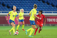 YOKOHAMA, JAPAN - AUGUST 6: Caroline Seger #17 of Sweden goes forward and Ashley Lawrence #10 looks on during a game between Canada and Sweden at International Stadium Yokohama on August 6, 2021 in Yokohama, Japan.