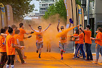 Man Running Through Orange Dye Color Zone, Seattle Center, Washington State, WA, America, USA.