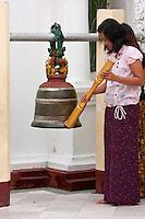Myanmar, Burma.  Shwedagon Pagoda, Yangon, Rangoon.  Worshiper Striking Temple Bell, an offering to the Buddhas and bodhisattvas.