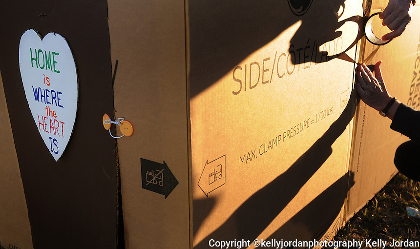 """Kelly.Jordan@jacksonville.com--111111--Lynette Weber, of Jacksonville is casts a shadow across her cardboard box home as she puts the finishing touches on her home as the sun sets. In an effort to raise money and bring awareness to homelessness Family Promise of Jax hosted Cardboard City, an opportunity for participants to experience what it is like to be homeless by sleeping in cardboard boxes Friday night, November 11, 2011. Despite a chilly forecast, participants set up their cardboard box houses at the CrossRoad Church on Gate Parkway on the Southside. This is the first time Weber has participated in the event, and says, """"I was thinking one whole night in the cold, I'm going to freeze. But I realized that every night they (the homeless) do.""""(The Florida Times-Union, Kelly Jordan)"""