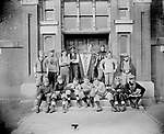 FOOTBALL TEAM AT EVERETT ELEMENTARY SCHOOL. Everett Elementary School was built in 1887 at Eleventh and C Streets. Harrison Johnson built his house two blocks away in 1891 and presumably his son, John, attended school here. The football team John Johnson photographed at the schoolhouse door proudly displays its Everett pennant. Although mixed in age, size, race, and equipment, another damaged negative shows the group lined up in football formation. One youth's striped-sleeve jersey resembles the uniform of the University of Nebraska team in that era. The African American man standing to the left of the pennant may be Pendleton Murray, who graduated from Lincoln High School in 1917 and worked as a carpet cleaner and later as a turnkey at the county jail. Everett Junior High School replaced this school in 1928, then was converted back into an elementary facility in 1990.<br /> <br /> Added by Stan Schmunk 6/2/2018: Pendleton's brother, whose name escapes me, was an even better athlete. He may be the one in one or both of these photos. Their father first appeared in Lincoln as midwife Hannah Rosier's assistant. He later owned a carpet laying business. The large family lived on the Southwest corner of 7th & C. It's still there. I saw it nearly every day when I was growing up at 720 C.<br /> <br /> Photographs taken on black and white glass negatives by African American photographer(s) John Johnson and Earl McWilliams from 1910 to 1925 in Lincoln, Nebraska. Douglas Keister has 280 5x7 glass negatives taken by these photographers. Larger scans available on request.