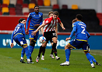 §20th March 2021; Brentford Community Stadium, London, England; English Football League Championship Football, Brentford FC versus Nottingham Forest; Vitaly Janelt of Brentford passing the ball into midfield as marked by Filip Krovinovic and James Garner of Nottingham Forest