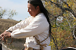 A Native American Indian man horseback riding on a pinto pony